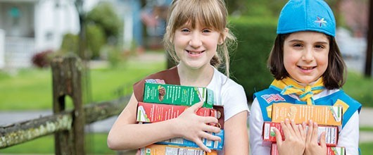 Girl Scouts holding cookie boxes